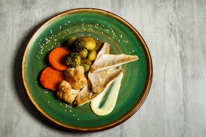 de hoogste mening over heerlijke stokvissenfilet met groenten en saus diende op groene plaat stock foto