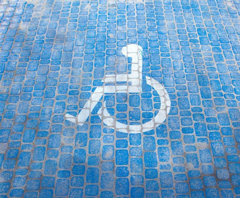 De hoogste mening over parkerenteken voor maakt mensen onbruikbaar Gehandicapte parkeerplaats en rolstoelsymbolen op bestrating stock foto's