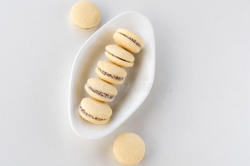 De hoogste mening van Alfajores, zandkoekkoekjes vulde met karamel en rolde in kokosnoot Argentijnse makarons op witte plaat stock foto