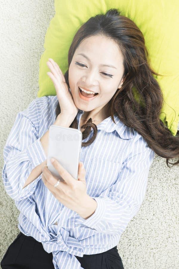 De hoogste mening van Aziatische vrouw neemt een selfie en het liggen op de vloer bij woonkamer stock foto