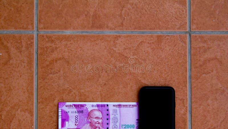 De hoogste mening van de nieuwe de muntrekening van Rs 2000 hield naast een smartphone De nieuwe rekening werd geïntroduceerd in  stock foto