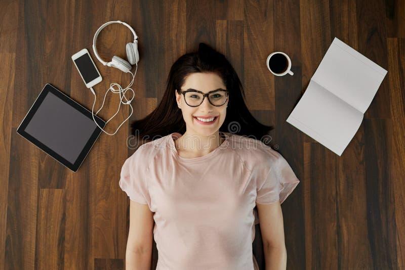 De hoogste mening van een positief meisje met glazenglimlachen ligt op floo royalty-vrije stock afbeelding
