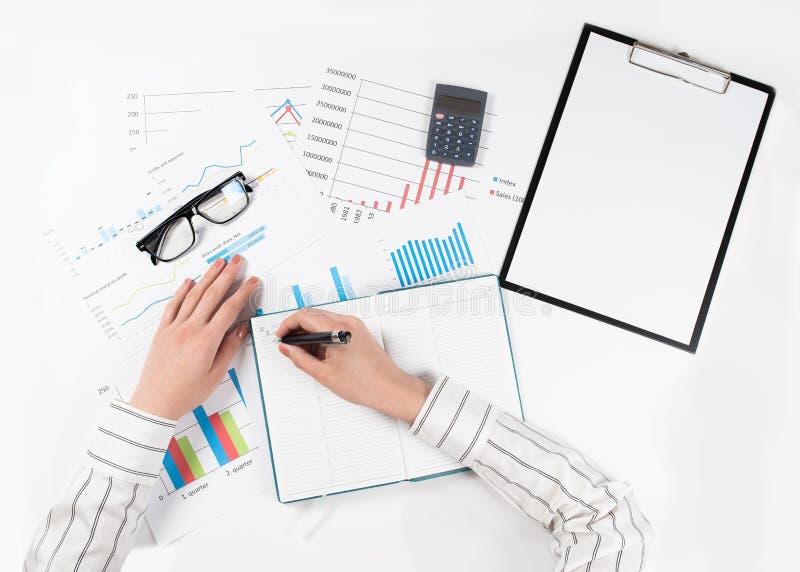 De hoogste mening van handen de bedrijfs van de vrouw maakt een financieel verslag op witte lijst stock fotografie