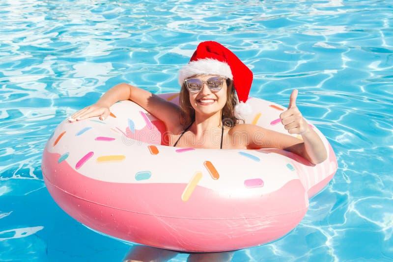 De hoogste mening van jong wijfje in Kerstmishoed zwemt met roze cirkel in pool stock afbeeldingen