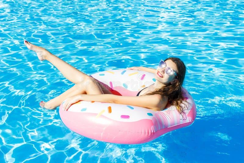 De hoogste mening van jong wijfje zwemt met roze cirkel in pool stock fotografie