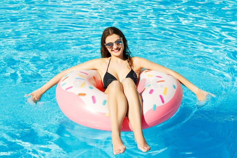 De hoogste mening van jong wijfje zwemt met roze cirkel in pool royalty-vrije stock fotografie