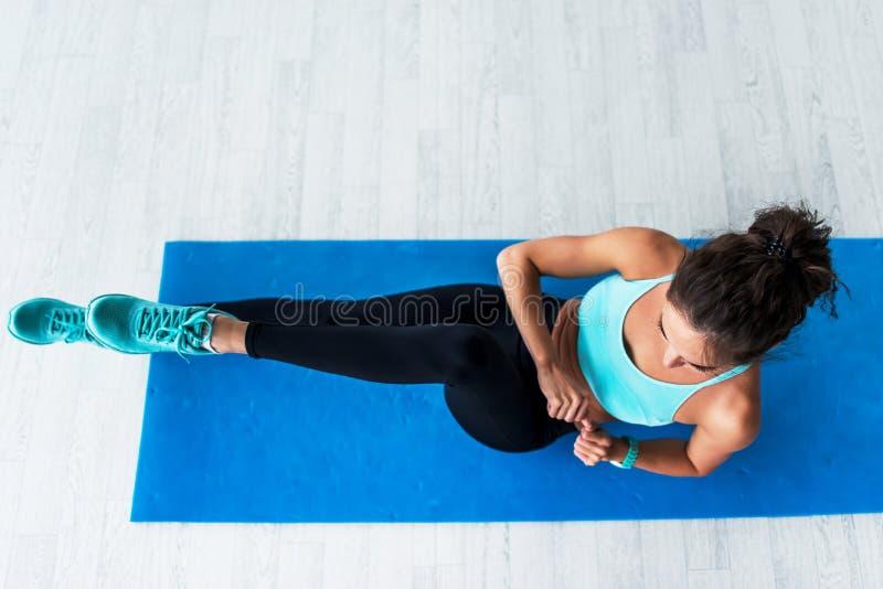 De hoogste mening van jongelui paste vrouw het uitwerken binnen doend fietskraken op blauwe mat stock fotografie