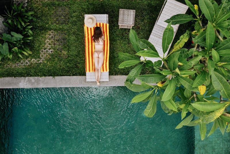 De hoogste mening van onherkenbare slanke jonge vrouw in het beige bikini ontspannen en zonnebaadt dichtbij luxe zwembad in groen royalty-vrije stock afbeeldingen