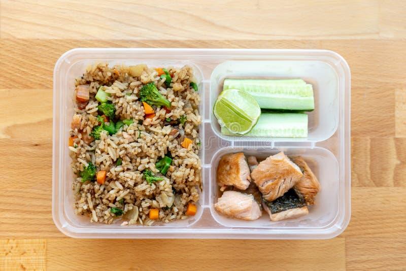 De hoogste mening van Organische gebraden zalm dobbelde lapje vlees met ui, broccoli en wortel gebraden rijst die met komkommer e royalty-vrije stock foto's