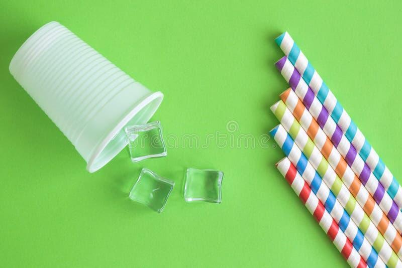 De hoogste mening van plastic kop met ijsblokjes en multicolored het drinken strosamenvatting isoleerde op groen stock afbeeldingen