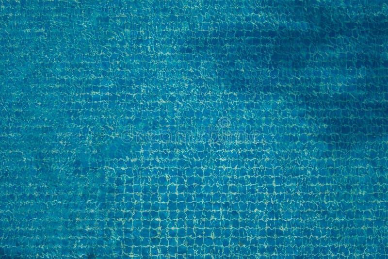 De hoogste mening van samenvatting vertroebelde textuur van blauw golfwater met mozaïektegels in zwembad stock fotografie