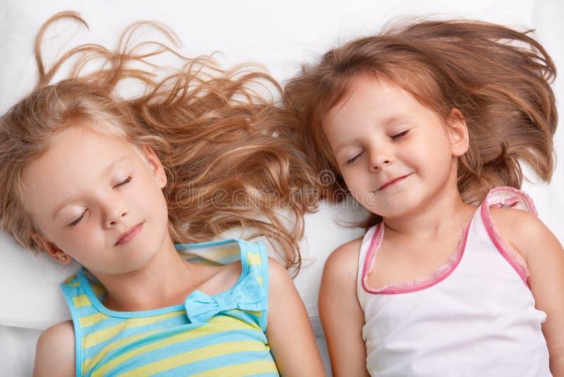 De hoogste mening van tevreden aantrekkelijke kleine meisjes of zustersglimlach samen, slaap in bed, ligt dicht aan elkaar, ziet  stock foto