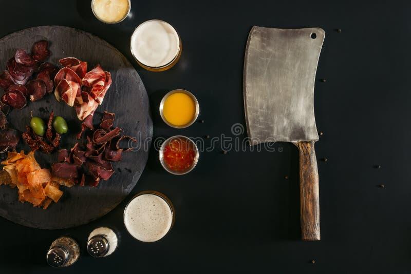 de hoogste mening van vleesmes en het gastronomische gesneden geassorteerde vlees op lei schepen met sausen en kruiden in stock fotografie