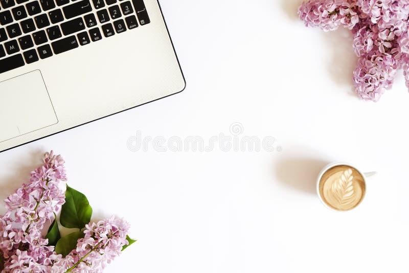 De hoogste mening van vrouwelijke werknemerdesktop met laptop, bloemen en verschillend bureau levert punten Vrouwelijke creatieve stock fotografie