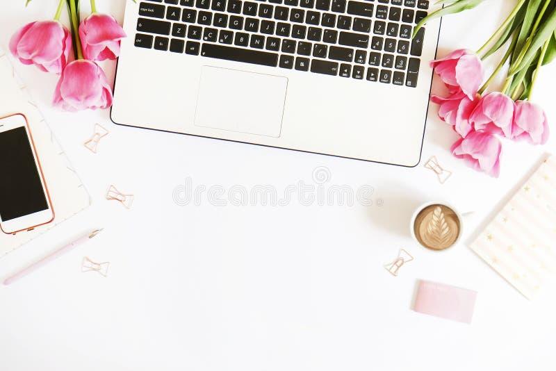 De hoogste mening van vrouwelijke werknemerdesktop met laptop, bloemen en verschillend bureau levert punten Vrouwelijke creatieve royalty-vrije stock afbeeldingen