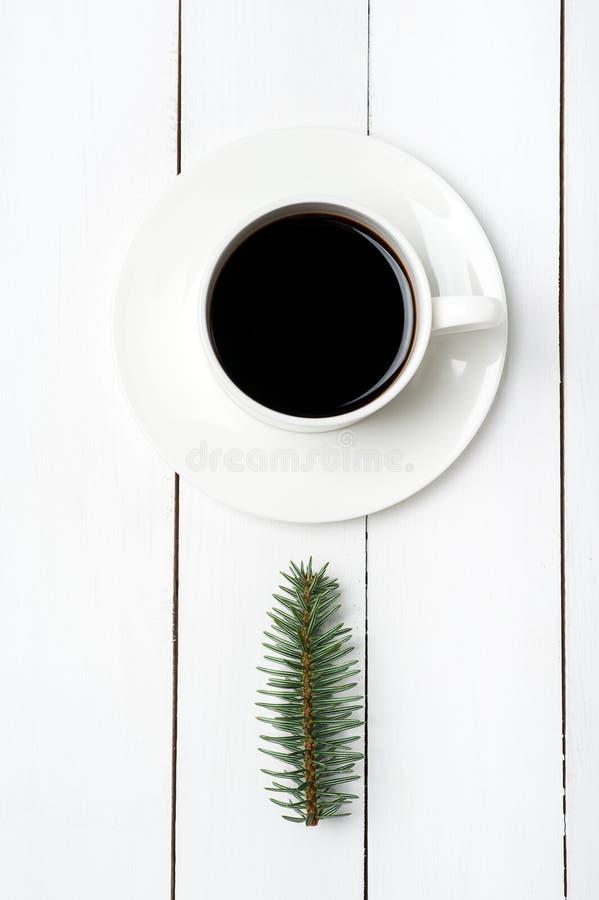 De hoogste mening van de wintersamenstelling van kop van koffie en de spar vertakken zich op witte houten achtergrond Kerstmisoch royalty-vrije stock foto