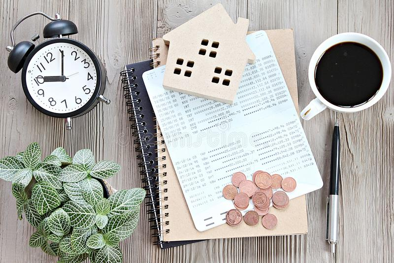 De hoogste mening of vlak legt van houten huismodel, spaarrekeningboek of financiële staat en muntstukken op bureaulijst royalty-vrije stock foto's