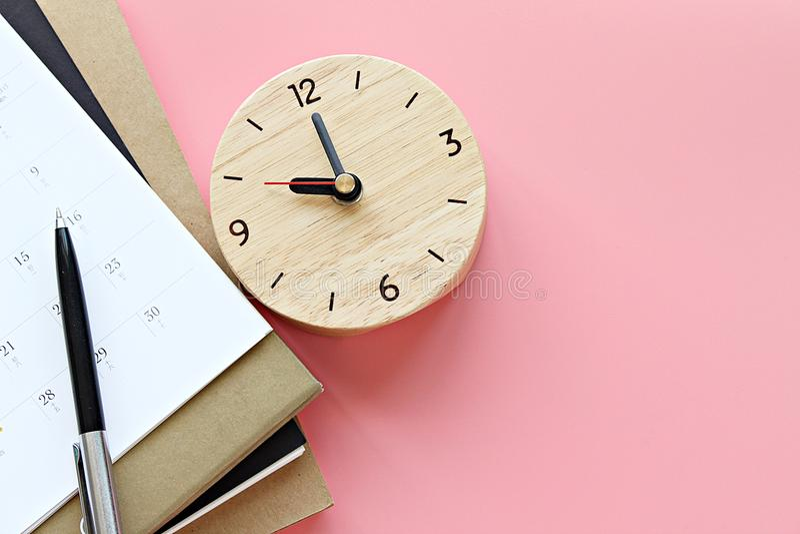 De hoogste mening of vlak legt van notitieboekjes, kalender, klok en pen op roze achtergrond royalty-vrije stock afbeeldingen