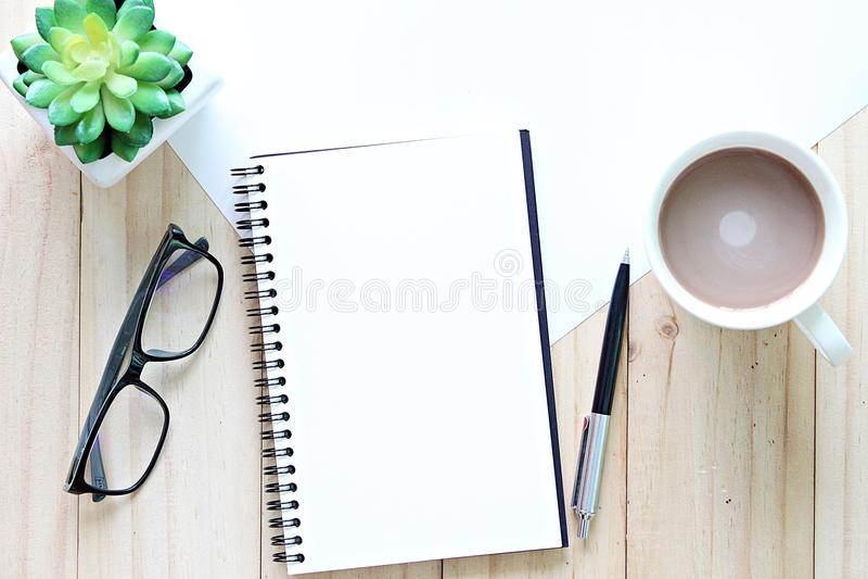 De hoogste mening of vlak legt van open notitieboekje met blanco pagina's en koffiekop op bureaulijst stock foto's