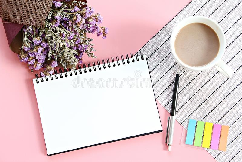 De hoogste mening of vlak legt van open notitieboekjedocument, boeket van droge wilde bloemen en koffiekop op bureaulijst stock foto