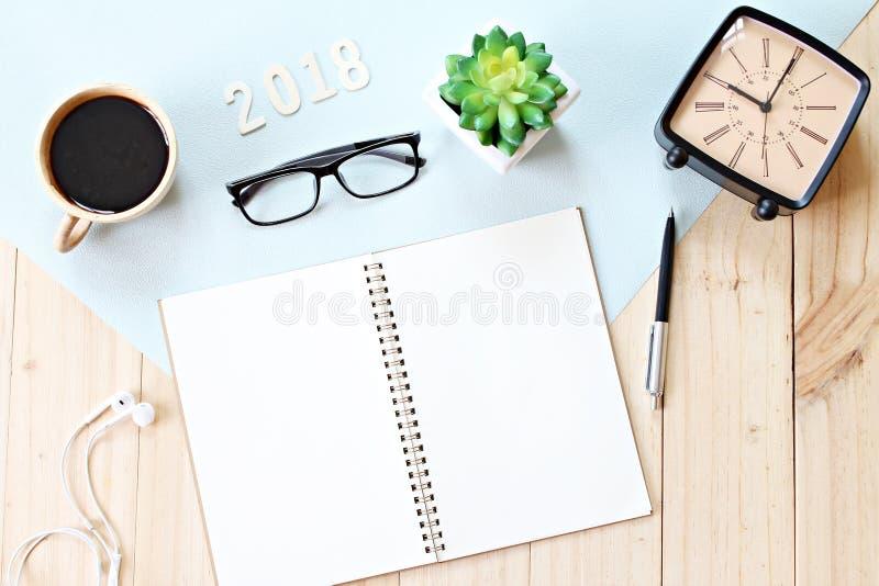 De hoogste mening of vlak legt van open notitieboekjedocument, toebehoren, houten nummer 2018 en koffiekop op houten achtergrond stock fotografie
