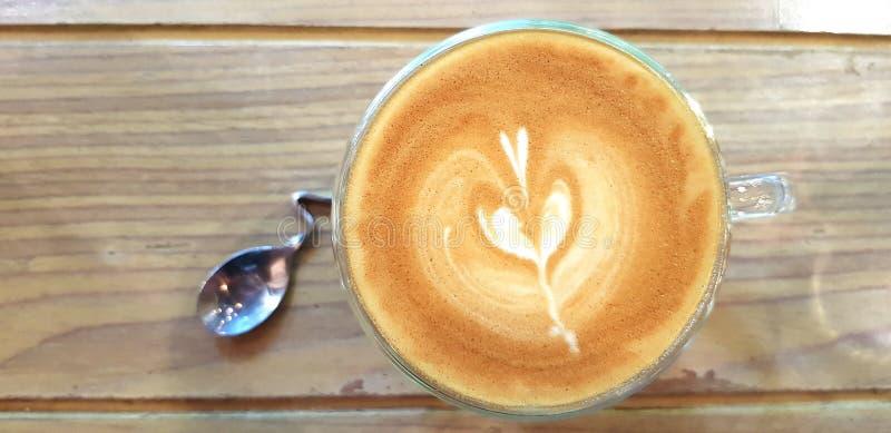 De hoogste meningskop van hete kunst latte koffie en het glas water met mooi ontwerp lepelen op houten lijst of achtergrond met e royalty-vrije stock foto's