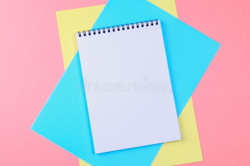 De hoogste meningsvlakte legt beeld met lege blocnotepagina en verschillende toebehoren op gekleurde oppervlakte stock afbeelding