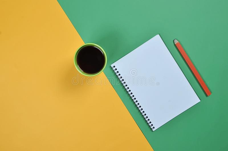 De hoogste meningsvlakte legt beeld met lege blocnotepagina, koffiekop, potlood en verschillende toebehoren op gekleurde oppervla stock afbeeldingen