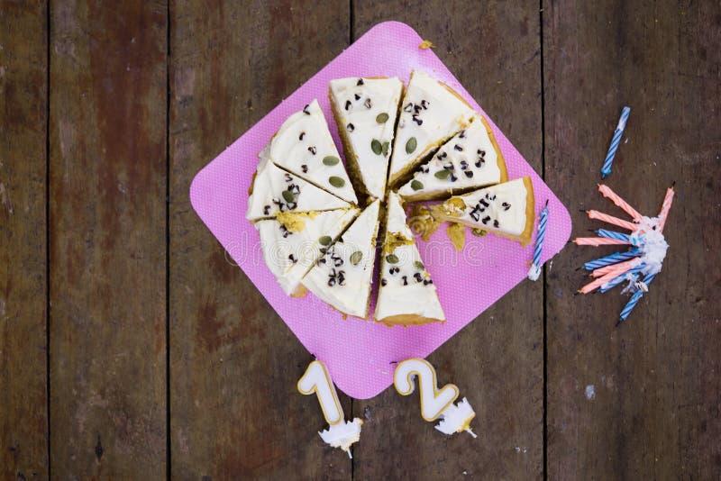 De hoogste meningsvlakte legt de gesneden eigengemaakte cake van de pompoenverjaardag met kaarsen op houten lijst royalty-vrije stock foto