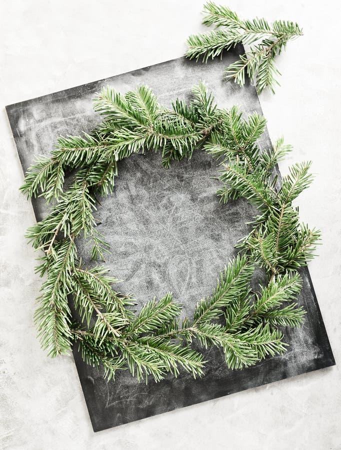 De hoogste meningsvlakte legt groene die Kerstmiskroon op bord met wit krijt wordt behandeld Het traditionele Nieuwe concept van  royalty-vrije stock afbeelding