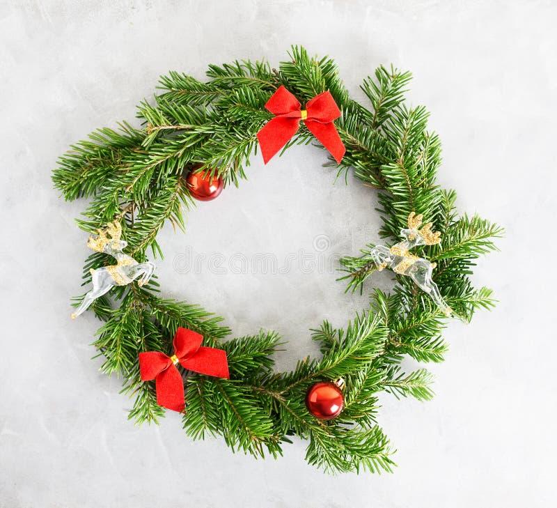 De hoogste meningsvlakte legt groene Kerstmiskroon met speelgoed en rode bogen op heldere achtergrond Het traditionele Nieuwe con royalty-vrije stock afbeeldingen