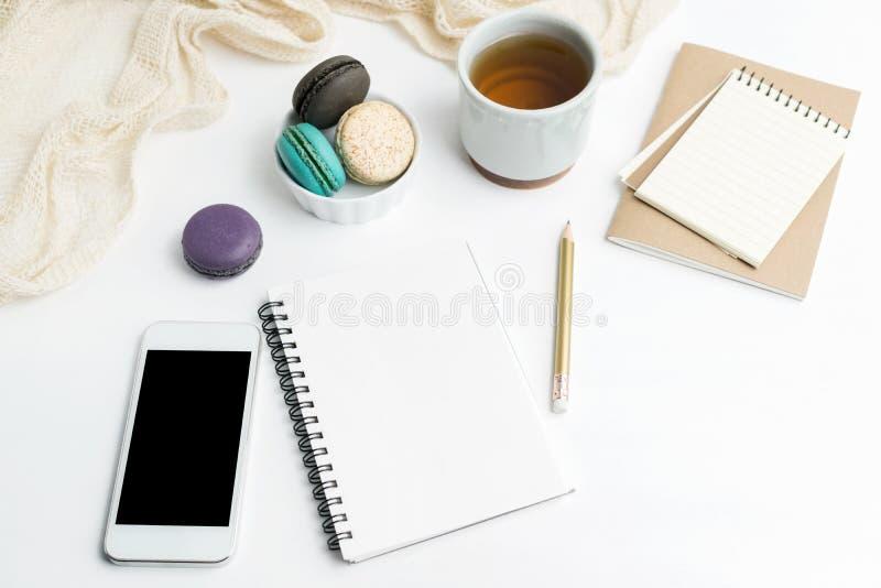 De hoogste meningsvlakte legt Leeg notitieboekje en celtelefoonmodel met macarons en theekop op witte achtergrond Kunst, het schr royalty-vrije stock foto
