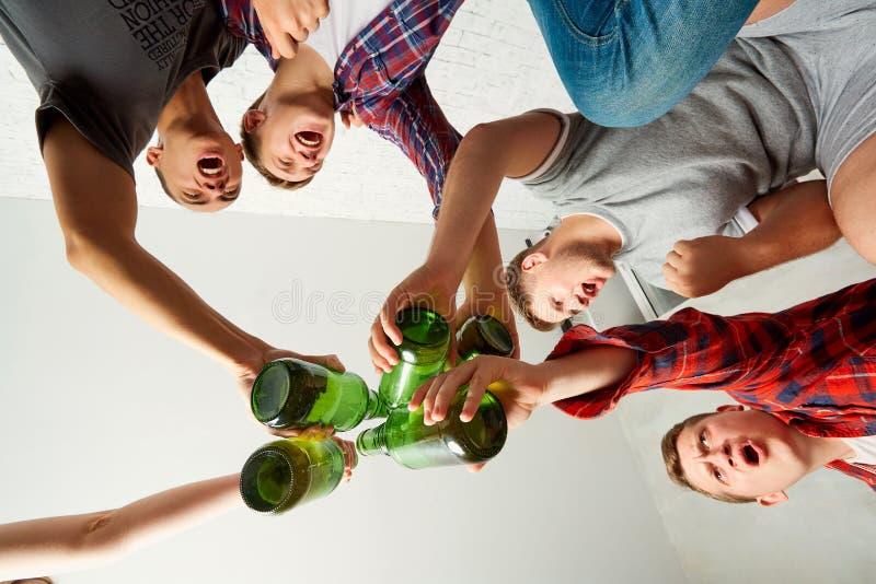 De hoogste meningsvrienden met een fles bier in zijn hand, clinked bott stock foto
