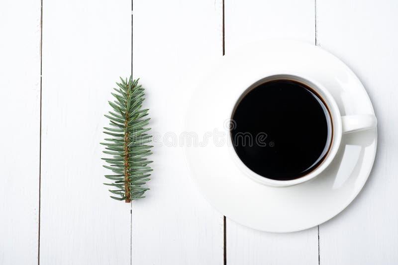 De hoogste samenstelling van de viewofwinter van kop van koffie en de spar vertakken zich op witte houten achtergrond Kerstmisoch stock afbeelding