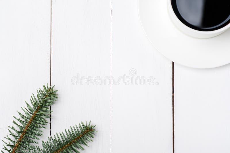De hoogste samenstelling van de viewofwinter van kop van koffie en de spar vertakken zich op witte houten achtergrond Kerstmisoch royalty-vrije stock fotografie