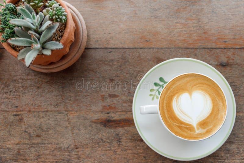 De hoogste van de de koffiemelk van de meningskunst latte vorm van het het schuimhart met cactus op w royalty-vrije stock fotografie