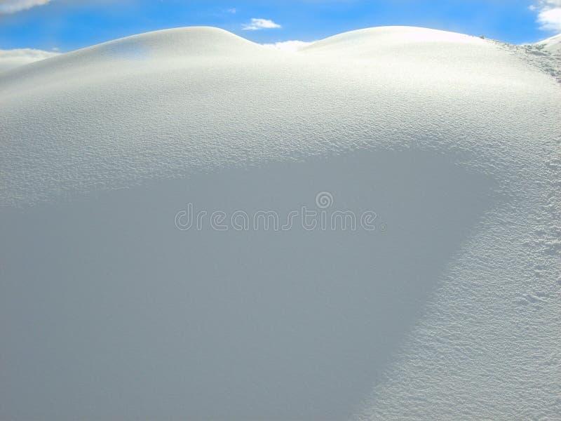 De hoop van de sneeuwbank geweven, met blauwe hemel stock afbeelding