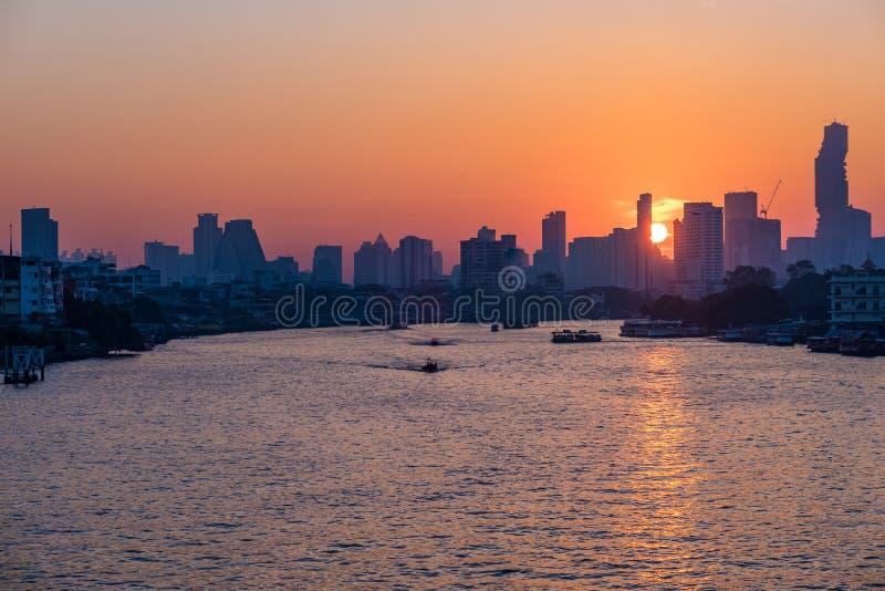 De horizon van Bangkok bij zonsopgang, hoofdstad van Thailand, toneelcityscape Boten die op Chao Phraya River kruisen stock foto