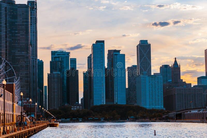 De horizon van Chicago van de pijler met zonsonderganghemel wordt bekeken in de rug die stock foto's