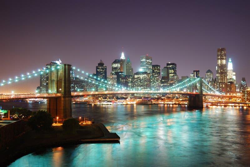 De Horizon van de Stad van New York bij nacht stock afbeelding