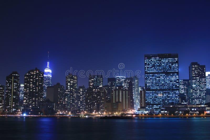De horizon van Manhattan bij Nachten stock afbeeldingen