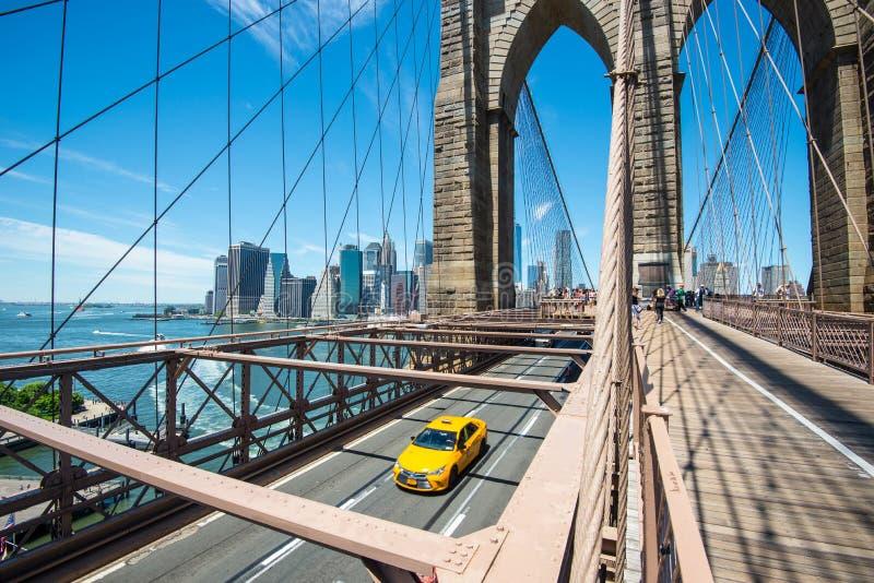 De horizon van New York Manhattan van de Brug van Brooklyn met gele taxi stock foto's