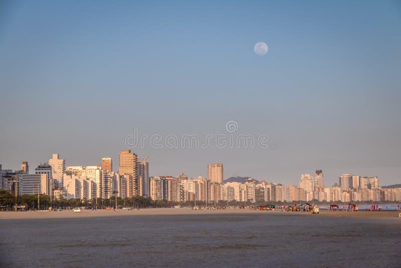 De horizon van Santos Beach en van de stad bij zonsondergang met volle maan - Santos, Sao Paulo, Brazilië stock foto's