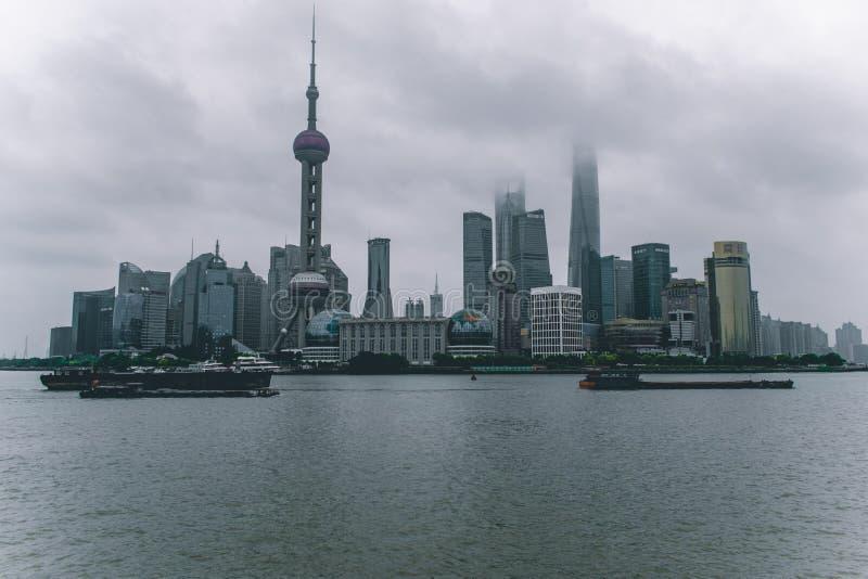 De horizon van Shanghai op een bewolkte die dag met de wolkenkrabbers in wolken en mist worden behandeld royalty-vrije stock afbeelding