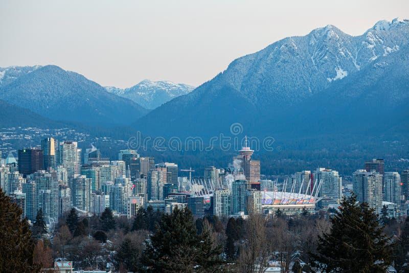 De horizon van Vancouver bij zonsopgang met bergen op achtergrond stock fotografie