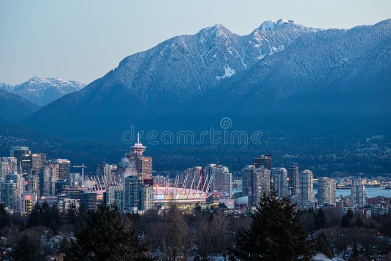 De horizon van Vancouver bij zonsopgang met bergen op achtergrond stock afbeeldingen
