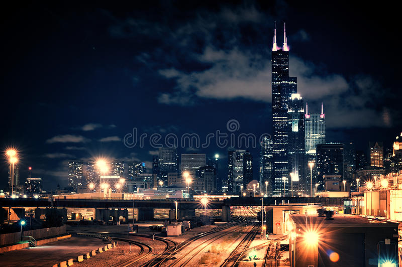 De horizoncityscape van Chicago bij nacht die een treinwerf kenmerken en ur stock fotografie