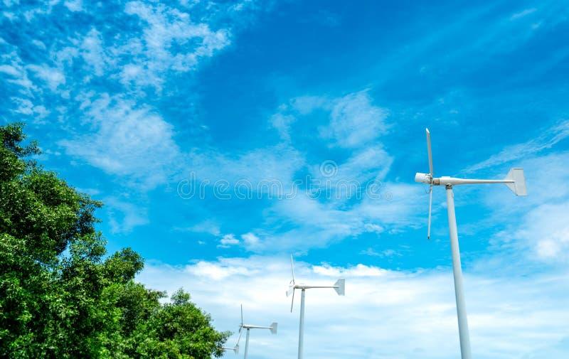 De horizontale turbine van de aswind met blauwe hemel en witte wolken dichtbij groene boom Windenergie in het landbouwbedrijf van stock foto