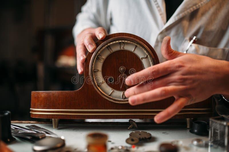 De horlogemaker herstelt oude houten lijstklok royalty-vrije stock afbeeldingen