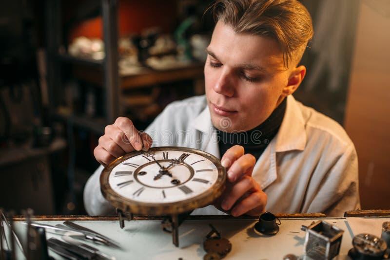 De horlogemaker past het mechanisme van oude horloges aan stock afbeelding